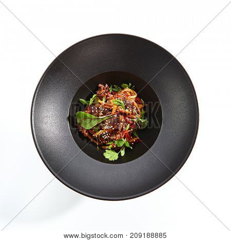 Udon noodles with beef and vegetables fresh greens and sprinkled with sesame seeds on black plate. Pan-Asian menu in restaurant. Top View