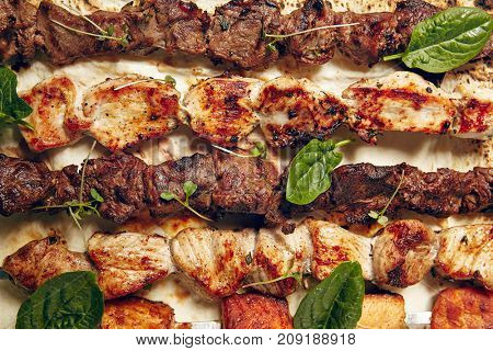 Chicken, Salmon and Meat Shish Kebabs on Parchment with Sauces. Top View