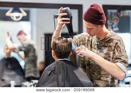 Handsome hairdresser dried hair. A young boy makes haircut in a luxury barbershop. Hairdresser making a hair style to cute guy.