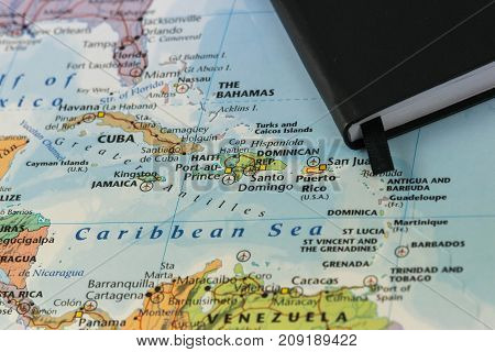 personal notes of someone planning a trip to the caribbean sea over a closeup map of Cuba, Haiti, Jamaica, Dominican, puertorico and the Bahamas.