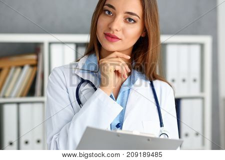 Beautiful female doctor hold in arms pad. Physical and patient disease prevention ward round exam in 911 er prescribe remedy for healthy lifestyle nurse consultant profession business concept
