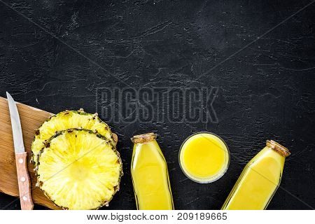 Preparing pineapple juice. Bottle with beverage near fruit slices and knife on balck background top view.