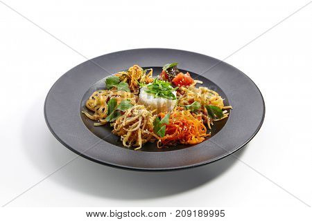 Set of vegetable snacks in Asian style with sesame and fresh herbs on an black plate. Pan-Asian cuisine in  restaurant.