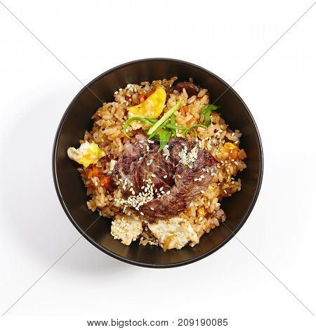Teppanyaki Fried rice with beef vegetables fresh herbs and seasonings in dark bowl on white isolated background. Pan-Asian cuisine in restaurant