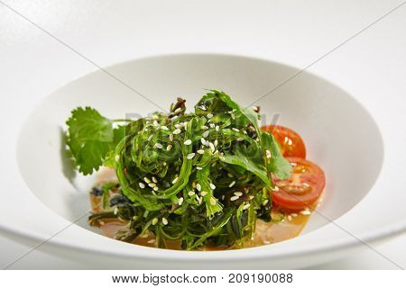 Pan-Asian menu in  restaurant. Hiyashi Wakame - Pickled seaweed with walnut sauce with sesame tomatoes and fresh herbs