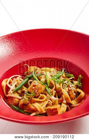 Pan-Asian cuisine menu. Noodles with slices of chicken and sprouted soybean slices of sprinkled greens and sesame seeds in red plate