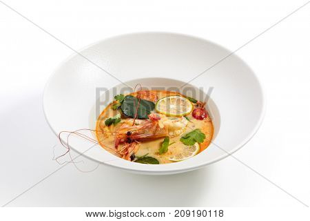 Tom yam kung - Thai soup with shrimp and coconut milk with slices of fruit and vegetables and fresh herbs in white plate. Pan-Asian menu in restaurant.