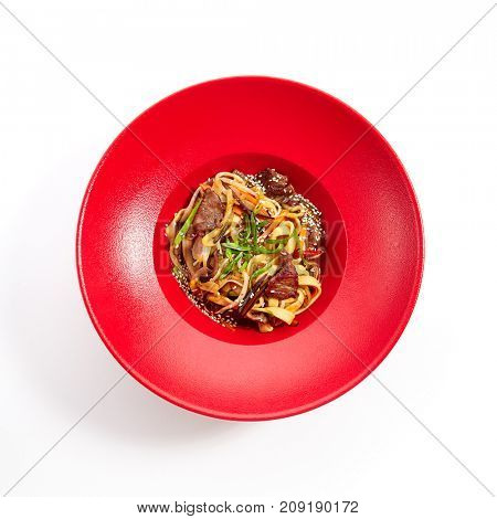 Udon noodles with beef and vegetables fresh greens and sprinkled with sesame seeds on red plate. Pan-Asian menu in restaurant. Top View