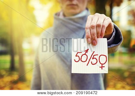 gender parity concept. close up young caucasian woman holding in hand paper with written text 50/50 with zeros as male and female gender symbols. Human rights day