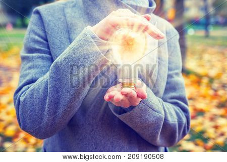 glowing lamp in hand of young woman in autumn park close-up. Idea fresh thought concept