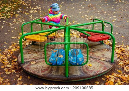 child is riding carousel in children's playground in autumn. Little girl playing
