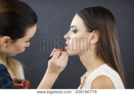 Make-up artist applies make-up to the young girl in the beauty studio. The concept of beauty. Profile.