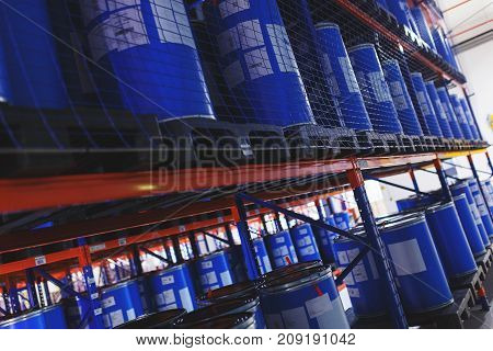 system of address storage of products, materials and goods in a warehouse. blue plastic barrels for storage of chemical liquids and products. Modern warehouse and storage systems.