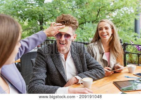 Big group of hilarious, beautiful young students relaxing, playing games at the cafe and sticking papers on foreheads on a blurred background.