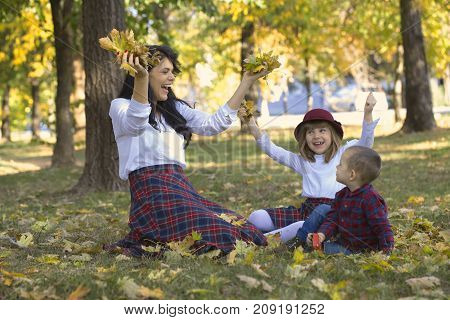 Beautiful Young Mother Plays With Her Children In The Park In Autumn