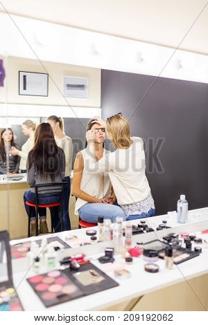 The make-up artist is applying make-up to the young girl in the beauty studio. The concept of beauty.
