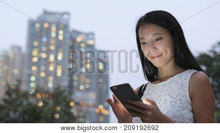 Woman using smart phone in city