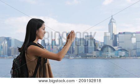 Traveler woman taking photo with cellphone in Hong Kong