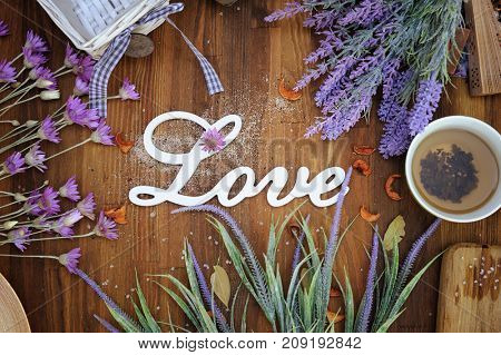 Vintage lavender flowers, cup of tea  and love text on a wood background