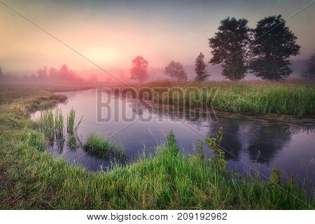 morning sunrise on scenic river. Landscape of beautiful misty nature at dawn. Colorful morning