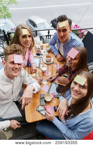Group of amazing, funny, cheerful friends having fun at the cafe on a blurred background. Teenagers playing a game with stickers on foreheads.