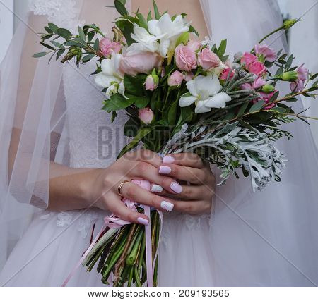 hands of the bride with beautiful manicure hold a beautiful wedding bouquet