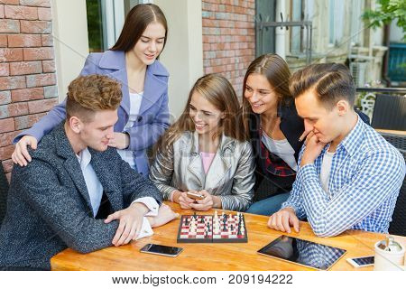 Five smart, gorgeous young friends playing chess on a blurred cafe background. A competitive team looking at the chess board and thinking.