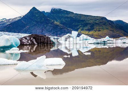 The largest glacier in Iceland - Vatnajokull. Huge ice floes have broken away from a glacier and drift towards the ocean. The concept of northern extreme tourism