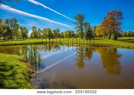 Shining sunny day in French Canada. Concept of recreational tourism.  Red and green autumn foliage reflected in small pond with a clay bottom