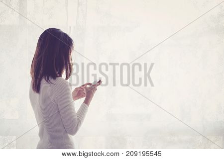 Beautiful Young Woman Asian Behind Holding Phone At A Window.