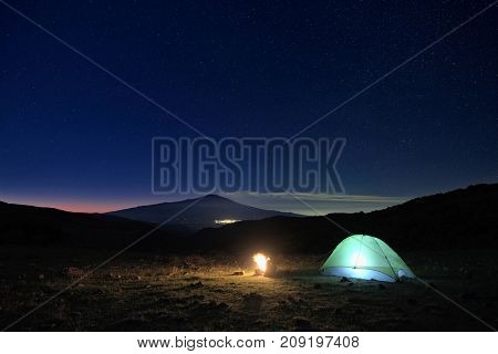 lighting tent, campfire and Etna Volcano at dawn from Nebrodi Park - Sicily