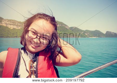 Vintage style young woman with eyeglasses smiling happily on the boat while cruising the natural of the sea and island in summer at Mu Ko Ang Thong National Park Surat Thani Thailand