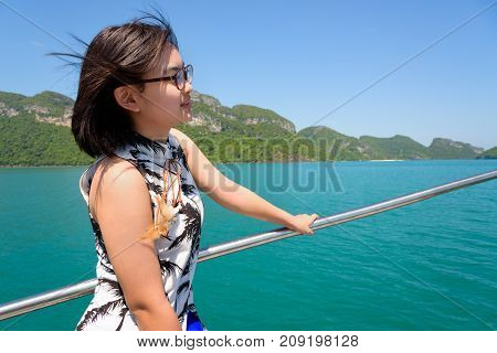 Cute young woman with eyeglasses smiling happily on the boat while cruising the beautiful natural of the blue sea and sky in summer at Mu Ko Ang Thong National Park Surat Thani Thailand