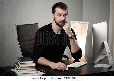 Smart businessman at workplace in office holding his head on hands. Sleepy worker early in the morning after late night work. Bisnanse and finance concept