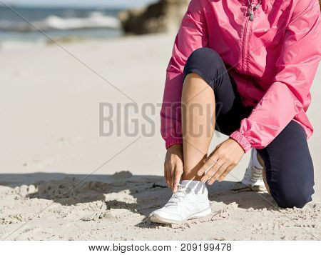 Woman runner tying shoelace at the seaside