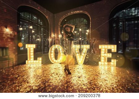 Beautiful girl posing against a background of shining letters. From the letters the word