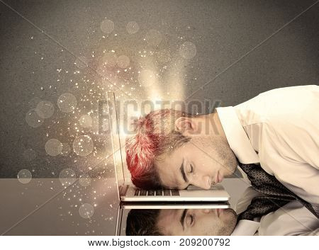 A young depressed business person laying his head on computer keyboard with thoughts exploding from his head illustrated by light beams concept