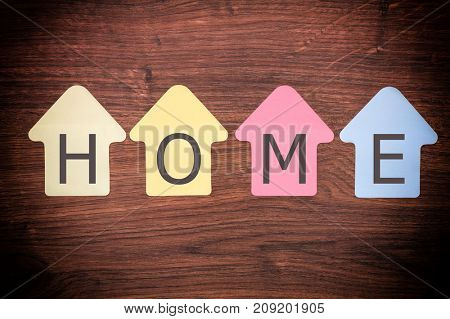 Home shaped stickers on wooden background and home text. Abstract home concept.