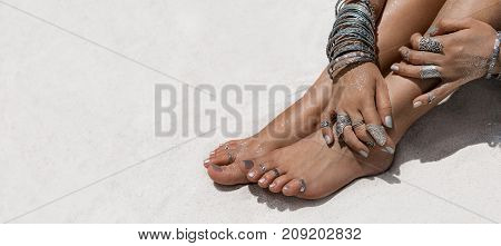 woman sitting on the sand hands and feet with ethnical accessories