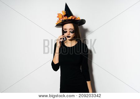 Halloween Witch with patches . Beautiful young woman in witches hat and costume. Wide Halloween party art design