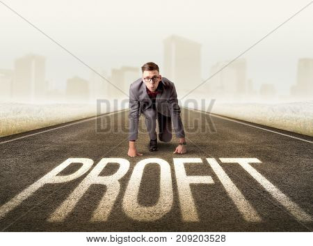Young determined businessman kneeling before profit sign