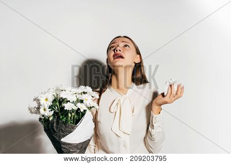 the girl is allergic to flowers. The girl is ill. The girl sneezes. Isolated on white background