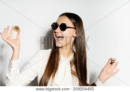 happy girl with glasses is holding coins. The girl won money. Bitcoins, crypto currency, electronic money.