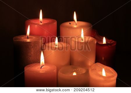 Group of burning candles in different heights and colors
