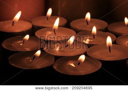 Big group of burning votive candles or votive lights