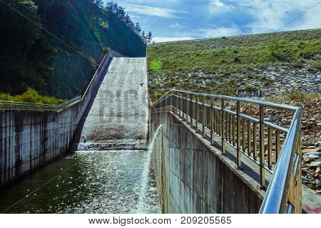 Landscape of water flowing down spillway into concrete waterway with chrome railing.