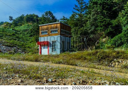 Square house with red awning over garage door in wooded area surrounded by green trees and flowers.