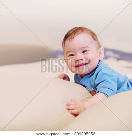 Happy smiling baby boy lie on a bed, looking at camera