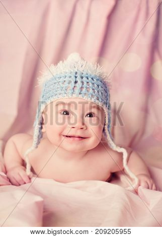 Beautiful happy and smiling baby lie on a stomach and looking at camera