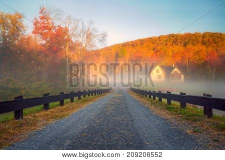 A fence lined lane leads into the fog with colorful foliage and blue skies in the background.
